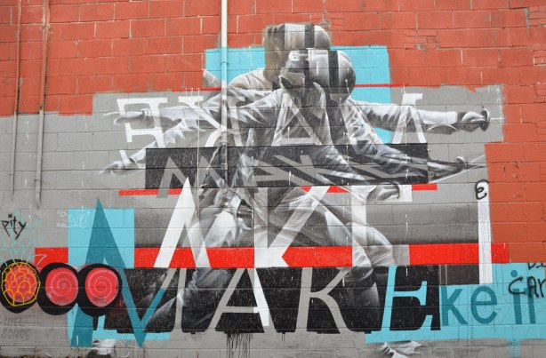 "mural of a fencer with sword drawn and ready.  The words are ""Make it"".  It is slightly abstracted and painted to look like there is motion in the picture."