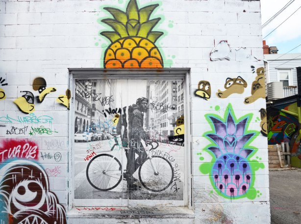 Square wheatpaste graffiti of a man on a bicycle on a city street.  Two large pineapples have been painted on the wall too, one above the bicycle man and one to the right.  The pineapples are bright colours, one is orange and yellow and the other is blue and purple.