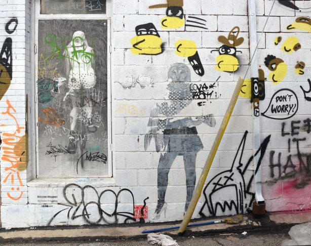 Wheatpaste and paper graffiti on a white concrete block wall.  A pair of yip yaps beside a person with an owl head and one wing instead of an arm.  The second arm is normal.   Also in the picture is a heatpaste black and white picture of a woman riding a bicycle away from the viewer.  She is wearing polka dot shorts.  Someone has also painted yellow and black bee like creatures with faces (black masks) and brown hats.