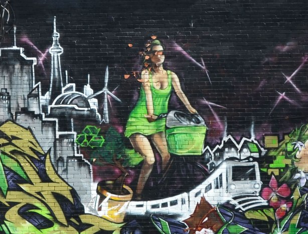 Part of a street art painting of  a woman on a bike with a Toronto scene behind her including the CN Tower and a TTC subway car below her.