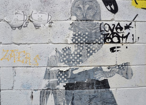 Wheatpaste and paper graffiti on a white concrete block wall.  A pair of yip yaps beside a person with an owl head and one wing instead of an arm.  The second arm is normal.