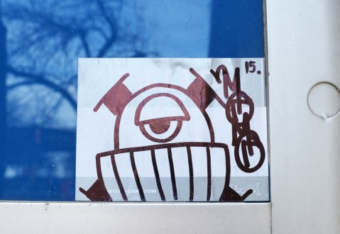 A sticker of a one eyed creature, black drawing on white, is on the blue part of a Bell payphone.
