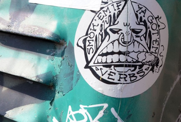 Sticker on a teal coloured metal box.  Sticker has triangle inside a circle.  The triangle is made into a face, big open mouth with cigarette clenched between the teeth.  Around the circle are the words 'Smok'em if ya got 'em. Verbs