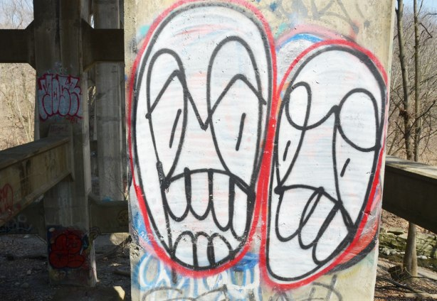 Two large abstract faces on a cement pillar.  The faces are white ovals, with a red outline.  THe features are in black line drawings