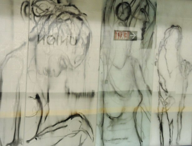 new art, pictures of people on the subway, on glass panels installed at Union Station platform - a sitting woman and a standing woman.  An exit sign is reflected in the glass