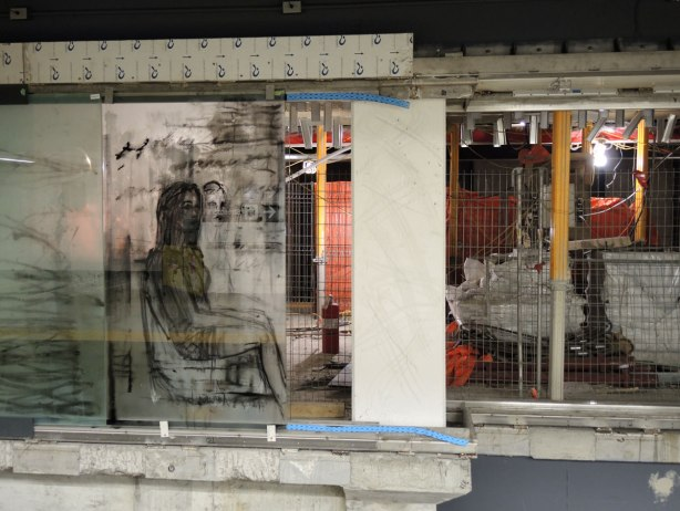 new art, pictures of people on the subway, on glass panels installed at Union Station platform - a seated woman picture on the left.  The panel on the right has not yet been installed, there is a space and the construction behind it is easily visible