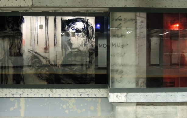 new art, pictures of people on the subway, on glass panels installed at Union Station platform, a woman's face in profile.  You can see traces of the construction behind her.