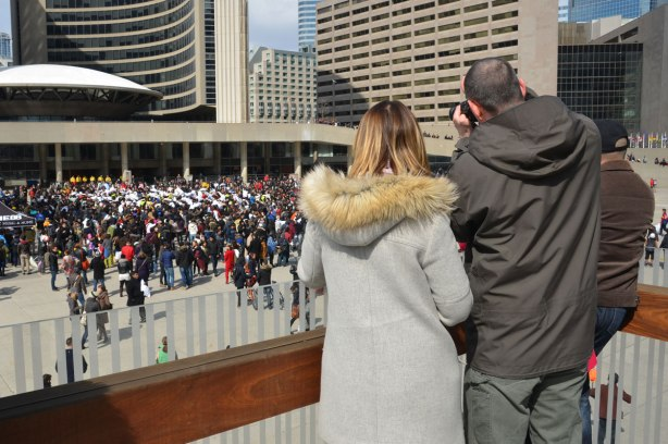 a couple taking photos from the upper level of Nathan Phillips square.  Down in the square below them is a large pillow fight, and a lot of spectators and photographers
