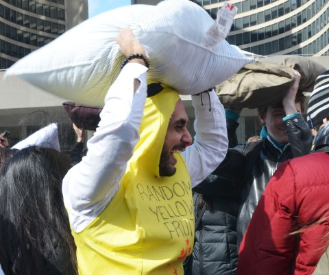 "Man wearing a yellow top with hood that says on the front ""Random yellow fruit"".  He's yelling and is holding a pillow over his head."