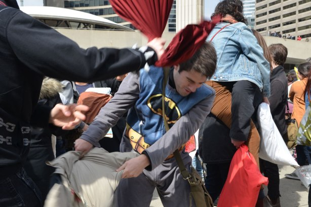 A young man in a batman shirt is being hit over the head with a red pillow in a large pillow fight.