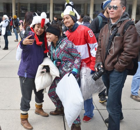 Three people in costumes are posing for a group selfie as a photographer walks past.