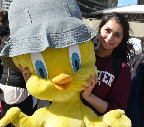 A young woman wearing a maroon McMaster shirt is holding a very large stuffed yellow cartoon character bird (tweety bird?)who is wearing a blue denim hat.  Posed for the camera.  Smiling.