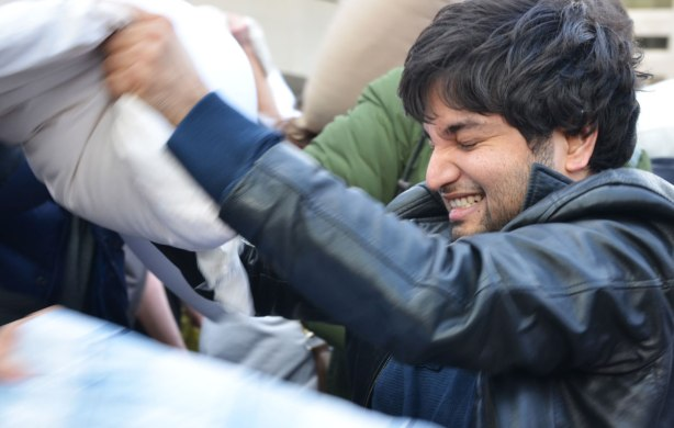 Young man in a black leather jacket has his eyes closed as he hits someone with a pillow in pillow fight.