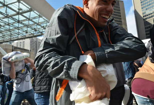 A smiling man, crouched shoulders, clutching a pillow, walks past a crowd in a pillow fight.