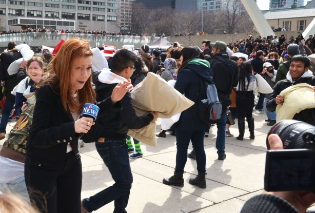 CTV reporter ducking pillows as she gives commentary.  Camera of cameraman is just in view on the right.   Crowd at the pillow fight is behind her.