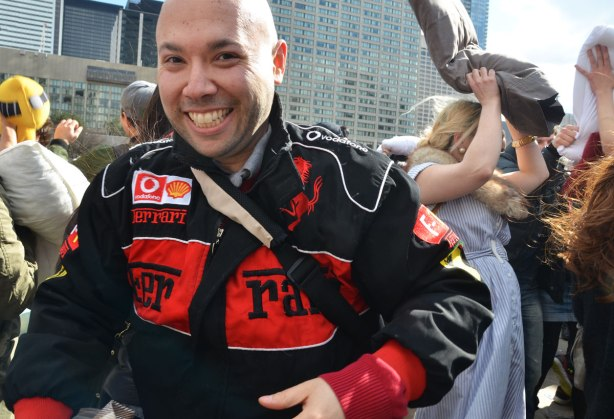 Bald man wearing a ferrari jacket is smiling at the camera as he walks through a crowd having a pillow fight