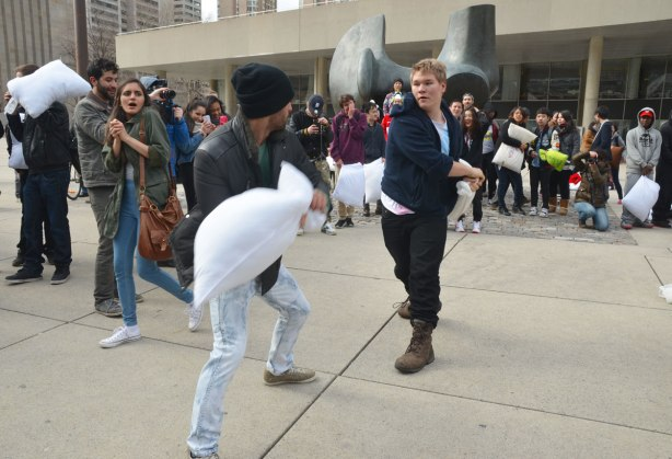 Two young men having a pillow fight while a crowd stands around them in a circle and watches.