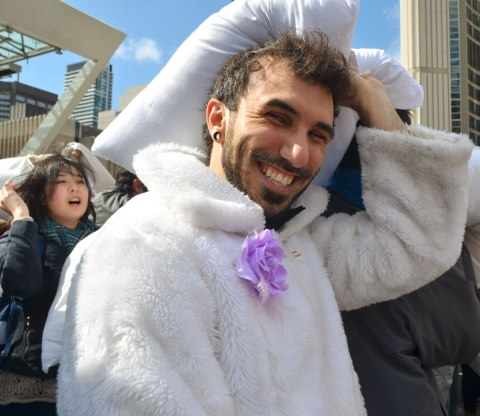 Man with a beard and a moustache, wearing a white fuzzy jacket with a pale purple artifical flower pinned to it. He's smiling and holding a pillow over his head.