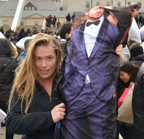 Young woman with long light brown hair is smirking at the camera and showing off her pillow - it is a body pillow with a picture of a male movie star on it and he's dressed in purple tux and black bow tie.