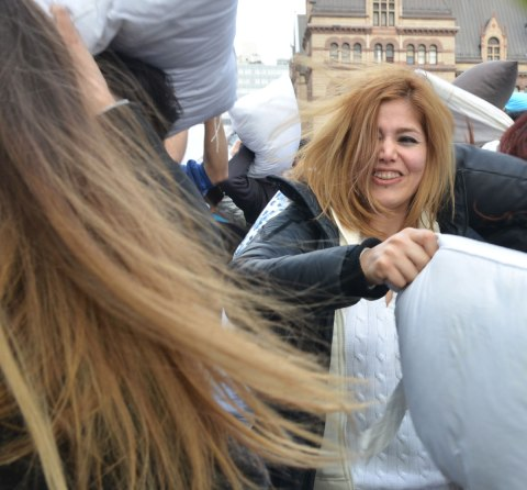 Two women in a pillow fight, lots of long hair blowing and being thrown around.