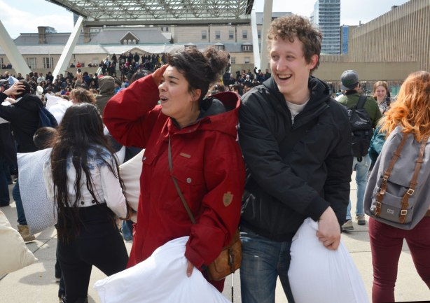A happy couple taking a break from a pillow fight.  He is laughing, she is saying ouch and putting her hand over her ear.