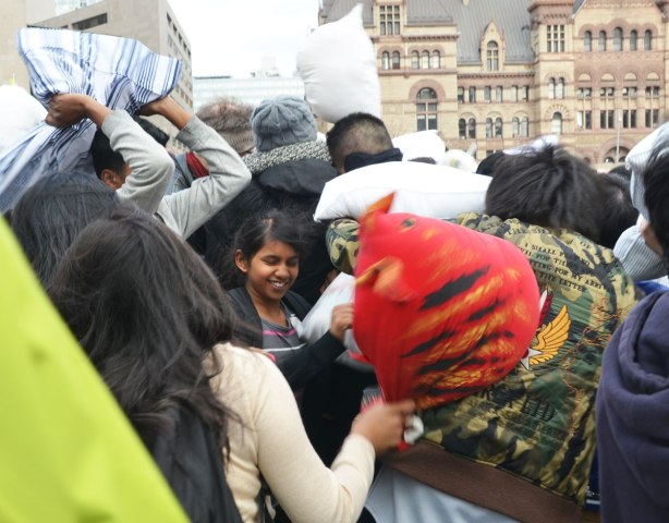 A young woman has her eyes closed and is smiling as the people around her are hitting each other with pillows.