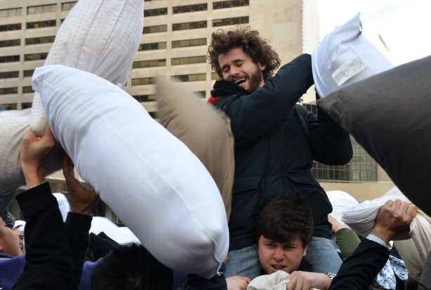 One young men is sitting on the shoulders of another.   He is swinging a pillow around in a pillow fight.   Many others, who are not on shoulders, are trying to hit him with pillows
