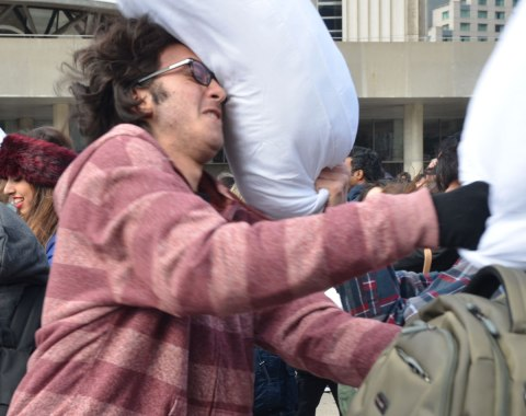 A man being hit in the face with a pillow