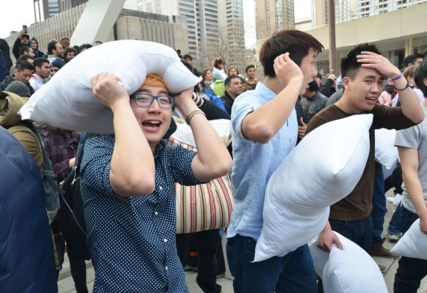Three young men are in the foreground, all are at a pillow fight.  One man, wearing glasses, has his pillow held tightly over his head, one is looking away from the camera and the third looks like his head hurts as he puts his hand on his forehead.