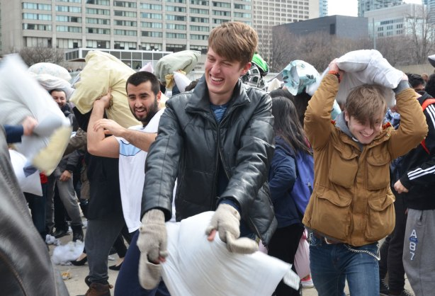 A group of young men enjoying a pillow fight as they swing their pillows at other people