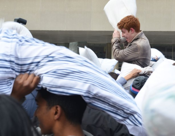 A young red headed man is on the shoulders of another person in a pillow fight.