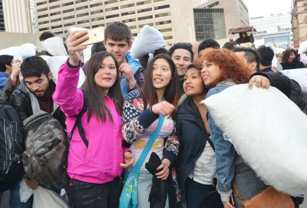A group of young people taking a selfie photo at a pillow fight.