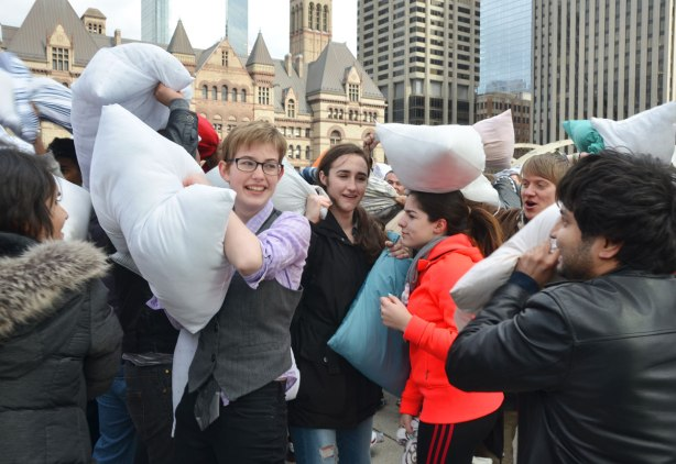 A groupd of young people in a crowd who are having a pillow fight at Nathan Phillips square.  Old city hall is in the background.