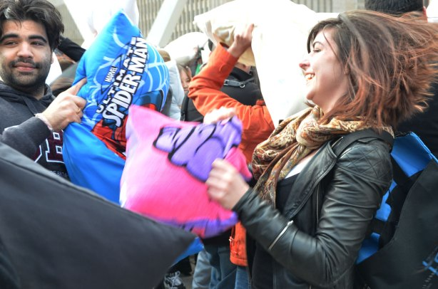 Man with a spiderman pillow and woman with a pink pillow at a pillow fight