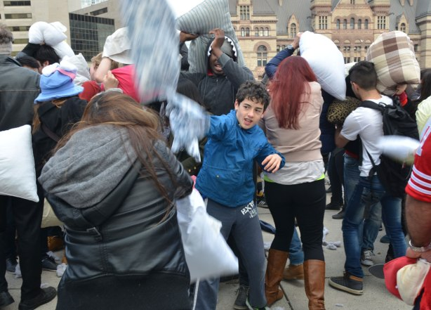 A boy in a blue jacket is in the foreground, he's hitting a woman in a black jacket. A group of young people in a crowd who are having a pillow fight at Nathan Phillips square.  Old city hall is in the background.