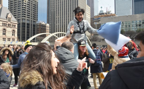 A young man on the shoulders of another at a pillow fight at Nathan Phillips Square.