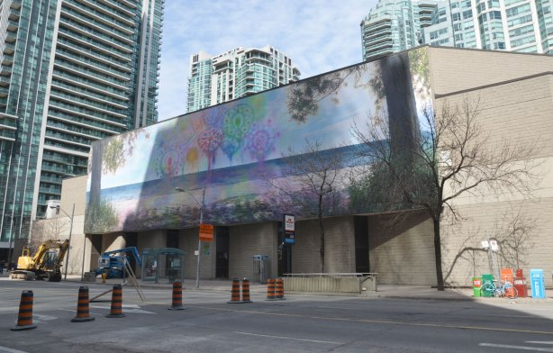 Very large photograph of a beach scene with sailboats out on the horizon and trees on both sides, superimposed with whimsical drawings of circles and swirls in blues, purples, greens, reds and yellows . It is mounted on the side of a two storey concrete building, the bunker like Westin Hotel and Conference Centre