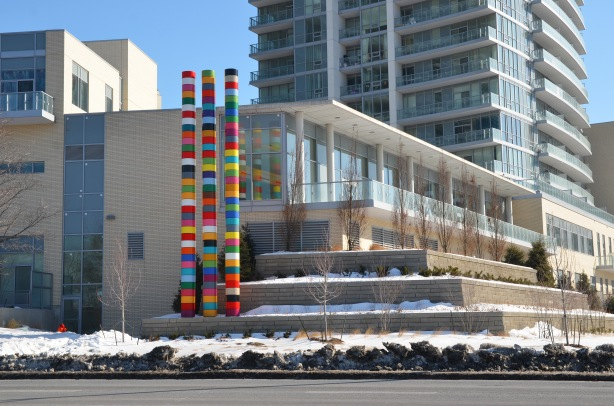 Looking across the street (Don Mills Rd) at a new condo development.  Three tall striped poles are beside one of the buildings as part of an art installation.  The building closest to the poles is low rise (2 or 3 storeys) but the building behind is a much taller structure.