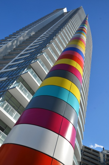 A brightly coloured striped cylindrical shaped pole in front of a tall condo building.