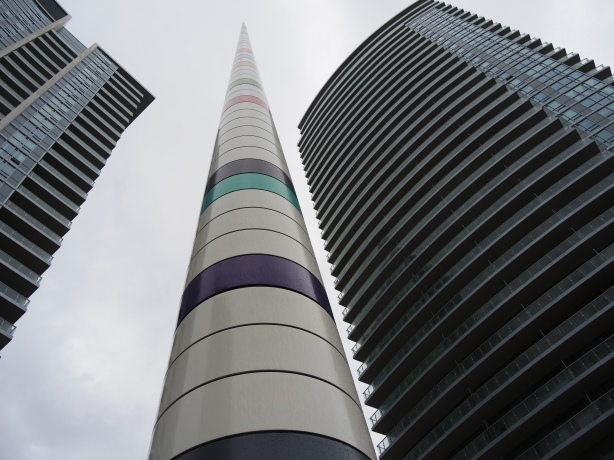 Very tall striped cylindrical pole with mostly white stripes with a few greys and only one or two pale colours.   Looking up from the base of it towards the tip, two tall condos, one on either side, are in the photo too.