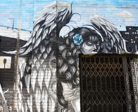 fallen angel mural in black and white on blue background - close up of the angel with an ugly face over a doorway.  Elaborate wings and a blue rose in her hair.