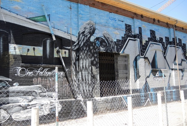 fallen angel mural in black and white on blue background - left hand side of the mural, old car, angel, and the word Los