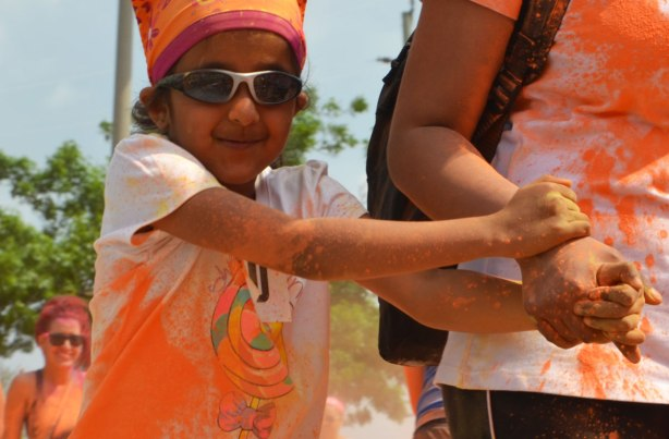 A child holds its mother's hand, color me rad run