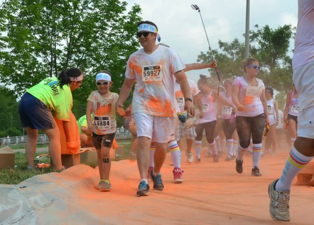 A child hold its father's hand, color me rad run