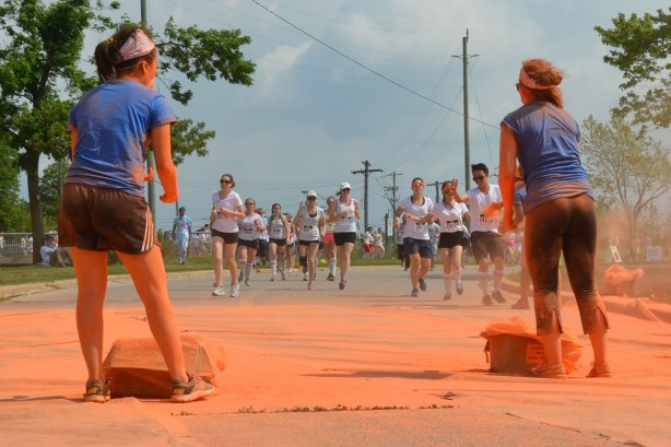 Two women wait with orange powder bombs in their hands, as a group of runners approach them, color me rad run