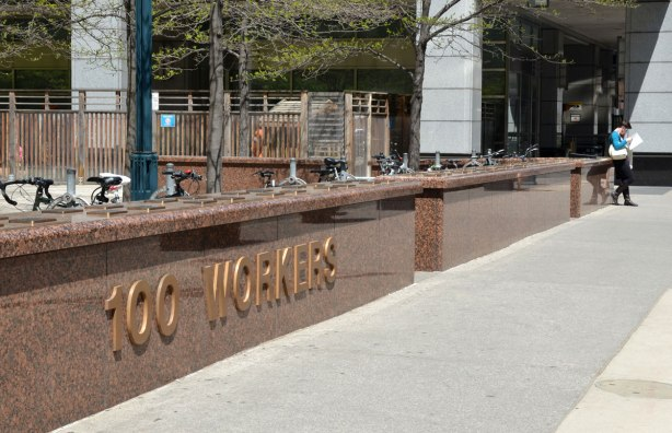 """low brown granite wall with large brass lettering on the front that says """"100 workers"""".  Along the top of the wall are plaques with names of people who died in the workplace between 1901 and 1999.  The name, year and cause of death is given on each plaque."""