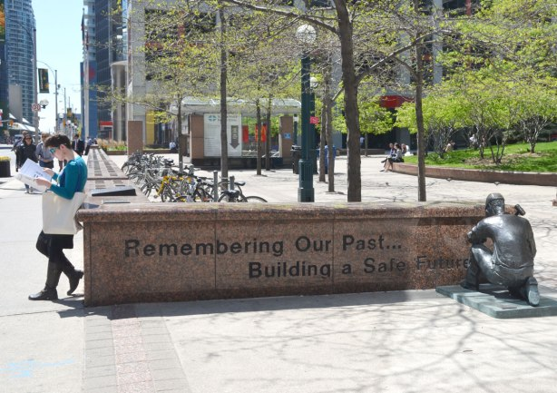 "view from the east of the 100 Workers memorial showing one of the half walls with the words"" Remembering our past.  Building a safe future.""  A lifesize statue of a workman chiseling words into the wall is on the right side of the photo."