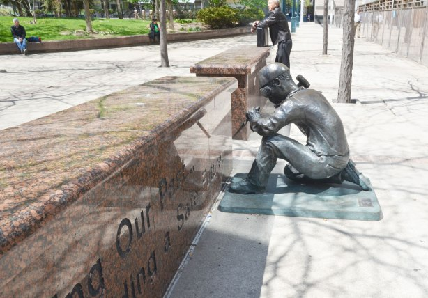 A statue of a workman chiseling out the words on a granite wall.