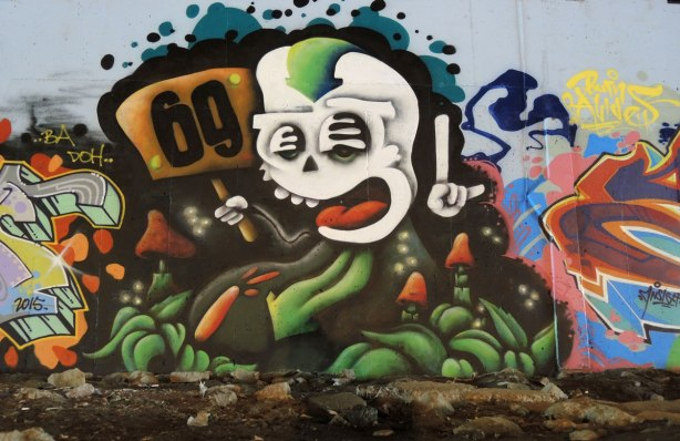 part of a mural under a bridge - a wacky white face with open mouth.  One hand of the creature is holding a sign that says 69 and the other hand has one finger pointed upwards