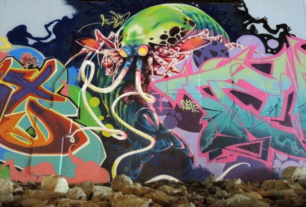 part of a mural under a bridge - large mantishrimp creature with long antennae (tentacles?) emerging from behind a tag